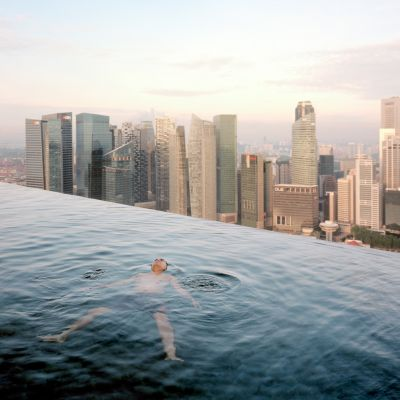 A man floats in the 57th-floor swimming pool of the Marina Bay Sands Hotel, with the skyline of the Singapore financial district behind him. Paolo Woods & Gabriele Galimberti, 2013, INSTITUTE